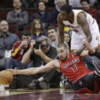 Photo - Toronto Raptors' Jonas Valanciunas (17), from Lithuania, stretches for the ball under pressure from Cleveland Cavaliers' Luol Deng, (9) from Sudan, during the first quarter of an NBA basketball game Tuesday, Feb. 25, 2014, in Cleveland. (AP Photo/Tony Dejak)
