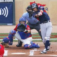 Photo - World's Jose Peraza, right, singles during the first inning of the All-Star Futures baseball game in front of United States' catcher Kevin Plawecki, Sunday, July 13, 2014, in Minneapolis. (AP Photo/Paul Sancya)