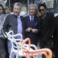 Photo -   French designer Philippe Starck, left, Kartell Home furniture company CEO Claudio Luti, center, and US rock star Lenny Kravitz look at chairs at the Kartell Home company space during Milan's Furnishing Accessories Exhibition, in Milan, Italy, Tuesday, April 17, 2012. The Milan furniture fair, a six-day event which ended Sunday, was full of experiment and whimsy. (AP Photo/Antonio Calanni)