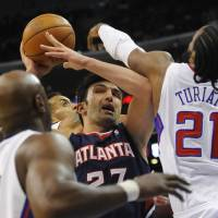 Photo -   Atlanta Hawks forward Zaza Pachulia (27), of Georgia, battles Los Angeles Clippers center Ronny Turiaf (21), of France, forward Matt Barnes, back center, and Lamar Odom, left, while driving to the basket in the first half of an NBA basketball game on Sunday, Nov. 11, 2012, in Los Angeles. (AP Photo/Gus Ruelas)