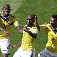 Photo - Colombia's Pablo Armero, center, celebrates with teammates, Victor Ibarbo, left, and Juan Cuadrado, right, after scoring during the group C World Cup soccer match between Colombia and Greece at the Mineirao Stadium in Belo Horizonte, Brazil, Saturday, June 14, 2014.  (AP Photo/Andrew Medichini)