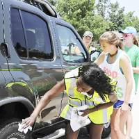 Photo - Chika Nwanebu, Hunter Hill, Katie Conrad and Maren Anderson dry a car during the fundraising car wash sponsored by Bishop McGuinness  Catholic High School students for a teacher who lost his home in the Moore tornado. Photo by M. Tim Blake, for The Oklahoman  M. Tim Blake - for The Oklahoman