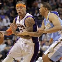 Photo -   Phoenix Suns small forward Michael Beasley (0) drives past Denver Nuggets point guard Andre Miller during the second half of a preseason NBA basketball game, Friday, Oct. 26, 2012, in Phoenix. (AP Photo/Matt York)