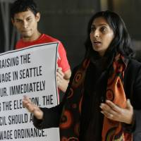 Photo - In this photo taken Nov. 4, 2013, Socialist candidate for Seattle City Council Kshama Sawant, right, speaks outside City Council chambers in Seattle about her support for raising the minimum wage to $15 an hour for all workers in the city. Sawant is challenging four-term Councilman Richard Conlin. (AP Photo/Ted S. Warren)