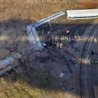 Photo - First responders gather at the derailment of a Metro North passenger train in the Bronx borough of New York Sunday, Dec. 1, 2013  The Fire Department of New York says there are