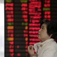 Photo - An investor looks at the stock bulletin board at a private securities company on Wednesday, March 6, 2013. The Dow's new all-time high and better economic data from the United States propelled Asian stock markets higher Wednesday. (AP Photo/Eugene Hoshiko)