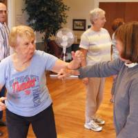 Photo -  Betty Windsor, left, and Patty Snyder practice self-defense techniques during a class taught by Gene Schultingkemper, a sixth-degree black belt, at the Edmond Senior Center. PHOTO BY PAUL HELLSTERN, THE OKLAHOMAN   PAUL HELLSTERN -