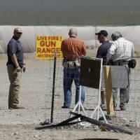 Photo - People are seen at the Last Stop outdoor shooting range Wednesday, Aug. 27, 2014, in White Hills, Ariz. Gun range instructor Charles Vacca was accidentally killed Monday, Aug. 25, 2014 at the range by a 9-year-old with an Uzi submachine gun. (AP Photo/John Locher)