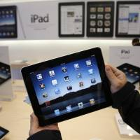 Photo - FILE - In this April 3, 2010 file photo showing customer uses an Apple iPad on the first day of Apple iPad sales at an Apple store in San Francisco. Apple said Monday, May 3, 2010, it has sold 1 million of its new iPad tablet computers in the month after its launch, meaning it's been selling more than twice as fast as the iPhone did when it was new.(AP Photo/Paul Sakuma, file) ORG XMIT: NYBZ140
