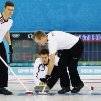 Photo - Denmark's skip Rasmus Stjerne Hansen, center, delivers the rock as Troels Harry, left, and Mikkel Poulsen, right, sweep the ice during the men's curling competition against Canada at the 2014 Winter Olympics, Thursday, Feb. 13, 2014, in Sochi, Russia. (AP Photo/Wong Maye-E)