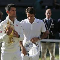 Photo - Novak Djokovic of Serbia, left, holds the trophy after defeating Roger Federer of Switzerland, right, in the men's singles final at the All England Lawn Tennis Championships in Wimbledon, London, Sunday July 6, 2014. (AP Photo/Ben Curtis)