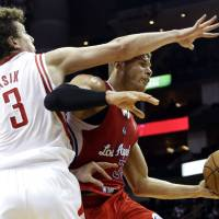 Photo - Los Angeles Clippers' Blake Griffin (32) is fouled by Houston Rockets' Omer Asik (3) during the first half of an NBA basketball game, Tuesday, Jan. 15, 2013, in Houston. (AP Photo/David J. Phillip)