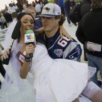 Photo - File-This Jan. 29, 2008 file photo shows Ines Gomez Mont, a reporter from TV Azteca in Mexico, wearing a wedding dress as she is carried by New England Patriots center Lonie Paxton while interviewing him during media day for the Super Bowl XLII football game in Glendale, Ariz.  Once a serious endeavor, media day is now a forum for credentialed