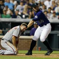 Photo - Colorado Rockies relief pitcher Tommy Kahnle (54) applies a late tag to the face of Washington Nationals' Ryan Zimmerman (11)  during the seventh inning of a baseball game on Monday, July 21, 2014, in Denver. Zimmerman scored on the play. (AP Photo/Jack Dempsey)