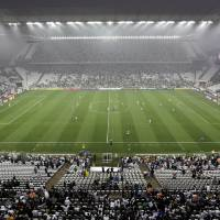 Photo - Corinthians's and Figueirense players battle it out during a Brazilian soccer league match at the Itaquerao, the still unfinished stadium that will host the World Cup opener match between Brazil and Croatia on June 12, in Sao Paulo, Brazil, Sunday, May 18, 2014. Only 40,000 tickets were put on sale for Corinthians' match against Figueirense because some of the 20,000 temporary seats needed for the World Cup opener are still being installed. (AP Photo/Andre Penner)