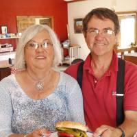 Photo - James and Sandra Stepp hold a burger made from all Oklahoma ingredients, including buffalo meat from their Sandy Springs Farms near Hinton.  Photo by Paul Hellstern, The Oklahoman  PAUL HELLSTERN -  Oklahoman