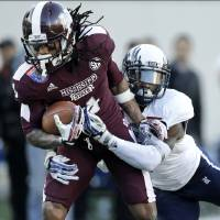 Photo - Mississippi State wide receiver Jameon Lewis, left, is brought down at the 2-yard line by Rice safety Julius White, right, in the second quarter of the Liberty Bowl NCAA college football game on Tuesday, Dec. 31, 2013, in Memphis, Tenn. Lewis gained 35 yards on the play. (AP Photo/Mark Humphrey)