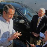 Photo - Mark Sanford speaks with a reporter as former S.C. Gov. Jim Edwards looks on during a campaign stop at a diner in Mount Pleasant, S.C., on Monday, May 6, 2012. Sanford faces Elizabeth Colbert Busch, the sister of comedian Stephen Colbert, in a special congressional election in the state's 1st District on Tuesday. (AP Photo/Bruce Smith)