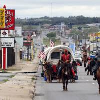 Photo - Above: The Sooner Teamsters and Trail Riders Association wagon train passes through downtown Purcell on Thursday.
