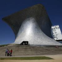 Photo -   People walk the stairs towards the main entrance to the Soumaya Museum in Mexico City, Monday, Nov. 19, 2012. On the northern edge of Mexico City's Polanco neighborhood, home to gleaming office towers, high-end restaurants and luxury boutiques, billionaire Carlos Slim has erected the mirrored, mushroom-shaped Soumaya museum, home to six floors of Impressionists, Old Masters, Mexican muralists, anonymous Mesoamerican craftsmen and hundreds of other works. The museum is open daily, from 10:30 a.m. to 6:30 p.m. and admission is free. (AP Photo/Marco Ugarte)