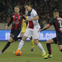Photo - Paris Saint Germain's Zlatan Ibrahimovic of Sweden, center, controls the ball past Nice's Mathieu Bodmer of France, left, during their French League One soccer match, in Nice stadium,southeastern France, Friday, March 28, 2014. (AP Photo/Lionel Cironneau)