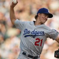 Photo - Los Angeles Dodgers starting pitcher Zack Greinke works against the Colorado Rockies in the fourth  inning of a baseball game in Denver, Thursday, July 3, 2014. (AP Photo/David Zalubowski)