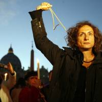 Photo - FILE - In this Dec. 6, 2008 file photo, Vladimir Luxuria, a former Communist lawmaker in the Italian parliament and prominent crusader for  transgender rights, mimics a hanging outside St. Peter's Square at the Vatican in Rome during a candlelight demonstration for gay rights. Luxuria said on her website and Twitter feed that she was detained by Russian police late Sunday night, Feb. 16, 2014, when she held up a gay rights banner near the Winter Olympic park in the Russian city of Sochi. (AP Photo/Alessandra Tarantino, File)