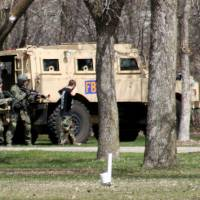 Photo - This May 3, 2013, photo provided by Jeremy Jones shows authorities with Buford Rogers, right, during a raid on a mobile home in Montevideo, Minn. Authorities said Monday, May 6, that Rogers was arrested, charged with one count of being a felon in possession of a firearm, and that the agency believes is disrupted a potential terror attack after a search of the home turned up Molotov cocktails, suspected pipe bombs and firearms. (AP Photo/Montevideo American-News, Jeremy Jones) MANDATORY CREDIT