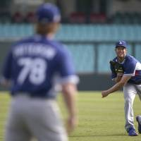 Photo - The Los Angeles Dodgers' Clayton Kershaw throws as his team trains at the Sydney Cricket Ground in Sydney, Tuesday, March 18, 2014. The MLB season-opening two-game series between the Los Angeles Dodgers and Arizona Diamondbacks in Sydney will be played this weekend. (AP Photo/Rick Rycroft)