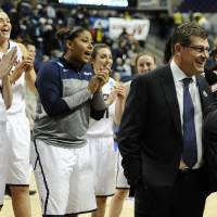 Photo - The Connecticut team sings Happy Birthday behind head coach Geno Auriemma, right, as he is interviewed on live television after their 87-44 win over Prairie View A&M in a first-round game of the NCAA women's college basketball tournament, Sunday, March 23, 2014, in Storrs, Conn. Today is Auriemma's 60th birthday. (AP Photo/Jessica Hill)