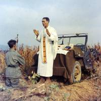 Photo - In this photo provided by Col. Raymond A. Skeehan, Father Emil Kapaun celebrates Mass using the hood of his jeep as an altar, as his assistant, Patrick J. Schuler, kneels in prayer in Korea on Oct. 7, 1950, less than a month before Kapaun was taken prisoner. Kapaun died in a prisoner of war camp on May 23, 1951, his body wracked by pneumonia and dysentery. On April 11, 2013, President Barack Obama will award the legendary chaplain, credited with saving hundreds of soldiers during the Korean War, the Medal of Honor posthumously. (AP Photo/Col. Raymond A. Skeehan via The Wichita Eagle)