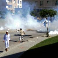 Photo -   Demonstrators throw stones during a protest against the anti-Islam film