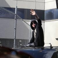 Photo - FILE - In this Thursday, Jan. 23, 2014 file photo, singer Justin Bieber waves from atop an SUV as he leaves the Turner Guilford Knight Correctional Center, in Miami. Bieber was released from jail following his arrest on charges of driving under the influence, driving with an expired license and resisting arrest. Bieber's court cases on both sides of the U.S.-Canadian border might not just lead to more scrutiny by judges and prosecutors, but could also complicate the pop star's jet-setting ways. (AP Photo/El Nuevo Herald, Hector Gabino, file) FLORIDA KEYS OUT, MAGS OUT, NO SALES. DIARIO LAS AMERICAS OUT