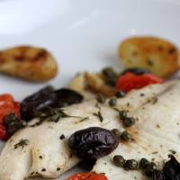 Photo - Mild-flavored tilapia is a forgiving ingredient and goes well with kalamata olives, tomatoes and fingerling potatoes. (Jessica J. Trevino/Detroit Free Press/MCT)