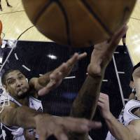 Photo - Phoenix Suns' P.J. Tucker, unseen with hand at center, reaches for the ball between San Antonio Spurs defenders Tim Duncan, left, and Manu Ginobili, right, of Argentina, during the first half of an NBA basketball game, Wednesday, Feb. 27, 2013, in San Antonio. Spurs' Tiago Splitter (22) watches.  (AP Photo/Eric Gay)