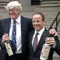 Photo - Florida billionaire William Koch, left, and his lawyer John Hueston hold bottles of wine outside Manhattan federal court, Friday, April 12, 2013, in New York. A Manhattan jury concluded the wines were sold to Koch fraudulently at a 2005 auction by a California businessman.  The jury awarded him $12 million Friday in punitive damages a day after awarding him $380,000 in compensatory damages. Koch said it's the best he's felt since winning the America's Cup in 1992.  (AP Photo/Larry Neumeister)