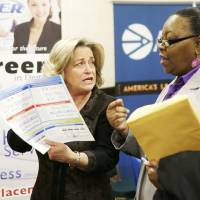 Photo - In this Wednesday, Jan. 22, 2014, photo, recruiter Valera Kulow, left, speaks with job seeker Monic Spencer during a career fair in Dallas. The Labor Department releases weekly jobless claims on Thursday, March 5, 2014. (AP Photo/LM Otero, File)
