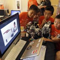 Photo - In this Aug. 14, 2013, photo, children look at a computer presentation on how to assemble Lego parts during a Digital Media Academy workshop in Stanford, Calif. Lego's new Mindstorms sets rolling out next month are keenly anticipated by Silicon Valley engineers_many of whom were drawn to the tech sector by the flagship kits that came on the market in 1998, introducing computerized movement to the traditional snap-together toy blocks and allowing the young innovators to build their first robots. (AP Photo/Marcio Jose Sanchez)