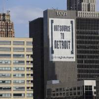 Photo - In this July 12, 2013, photo an Outsource to Detroit banner from Galaxe.Solutions is seen on a Detroit building. State-appointed emergency manager Kevyn Orr on Thursday, July 18, 2013, asked a federal judge permission to place Detroit into Chapter 9 bankruptcy protection.. (AP Photo/Carlos Osorio)