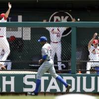 Photo - A ball hit by St. Louis Cardinals' Matt Carpenter lands in the Cardinals' bullpen for a solo home run as New York Mets right fielder Curtis Granderson, front, gives chase during the first inning of a baseball game Wednesday, June 18, 2014, in St. Louis. (AP Photo/Jeff Roberson)