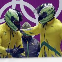 Photo - The team from Jamaica JAM-1, piloted by Winston Watts and brakeman Marvin Dixon, prepare to start their first run during the men's two-man bobsled competition at the 2014 Winter Olympics, Sunday, Feb. 16, 2014, in Krasnaya Polyana, Russia. (AP Photo/Dita Alangkara)