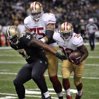 Photo -   San Francisco 49ers running back Kendall Hunter (32) rushes past New Orleans Saints outside linebacker David Hawthorne (57) as San Francisco 49ers guard Alex Boone (75) blocks in the second half of an NFL football game at the Louisiana Superdome in New Orleans, Sunday, Nov. 25, 2012. (AP Photo/Bill Feig)