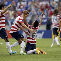 Photo - Teammates celebrate with United States' Joe Corona (6) after he scored a goal against El Salvador during the first half in the quarterfinals of the CONCACAF Gold Cup soccer tournament on Sunday, July 21, 2013, in Baltimore. (AP Photo/Patrick Semansky)