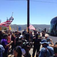 Photo - Protesters stand in the road blocking a bus carrying 140 immigrants on the way to be processed at the Murrieta border patrol station on Tuesday, July 1, 2014. The immigrants are bused to a border patrol facility in Murrieta, about an hour north of San Diego, for processing. Federal immigration authorities there will determine whether they will be held or released pending deportation proceedings.(AP Photo/The Press-Enterprise, Sarah Burge) (AP Photo/The Press-Enterprise, )  MAGS OUT; MANDATORY CREDIT
