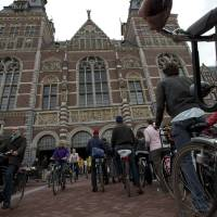 Photo - Hundreds of bicycles queue to pass  through Rijksmuseum, in Amsterdam, Netherlands, Monday May 13, 2013, signaling the end of more than a decade of efforts by cyclists to ensure a passageway that runs under and through the Rijksmuseum would remain open to bike traffic. The museum, which houses masterpieces by Rembrandt van Rijn and Vincent van Gogh, among others, opened last month after a 10-year renovation. Architects and successive museum directors had opposed allowing bikes through, and a local government tried to have them barred on safety grounds. But in a city that has more bicycles than people, the bike lobby prevailed. (AP Photo/Peter Dejong)