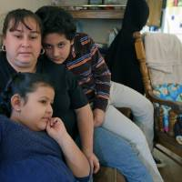 Photo - In this Feb. 28, 2013 photo, Sarah Chavez, center, sits with her son Bidal, right, and daughter Sarahi, front, at her home in Lexington, N.C. Desperate to raise money for their 6-year-old daughter's cancer treatments last summer, friends told Jose and Sarah Chavez of a way to quickly turn their meager savings into a small fortune. But what the Chavez family and many others didn't know was that state and federal regulators for months had received complaints that ZeekRewards was a scam. (AP Photo/Chuck Burton)