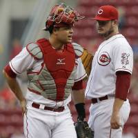 Photo - Cincinnati Reds starting pitcher David Holmberg, right, talks with catcher Devin Mesoraco in the first inning of a baseball game against the Atlanta Braves, Thursday, Aug. 21, 2014, in Cincinnati. (AP Photo/Al Behrman)