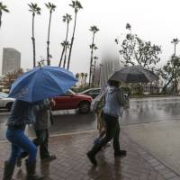 Photo - Heavy fog obscures the tops of buildings as pedestrians pass by in a rainstorm Friday Nov. 30, 2012 in Los Angeles. A series of storm systems will continue to move across southwestern Calif.,  through Monday morning. (AP Photo/Damian Dovarganes)