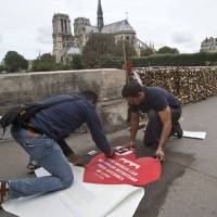 Photo - Municipality workers fix a giant sticker on the sidewalk of the Pont de l'Archeveche in Paris, Wednesday, Aug. 13, 2014. Paris is hoping to persuade visiting couples to end the recent and unwelcome tradition of fixing padlocks to the Pont de l'Archeveche. With giant stickers in three languages in French, English and Spanish. Paris began its 'Lovewithoutlocks' campaign, saying the city's famed bridge could not withstand the thousands of padlocks that cling to every available surface. (AP Photo/Michel Euler)