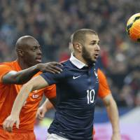 Photo - Karim Benzema of France, right, and Netherlands' Bruno Martins Indi eye the ball during the international friendly match between France and Netherlands at the Stade de France stadium, outside Paris, Wednesday, March 5, 2014. (AP Photo/Christophe Ena)